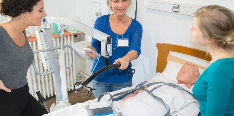 Nurses Lifting A Dummy On Bed