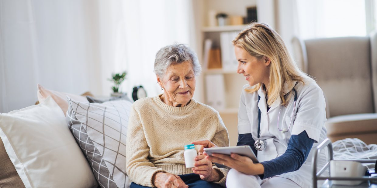 A,Health,Visitor,With,Tablet,Explaining,A,Senior,Woman,How